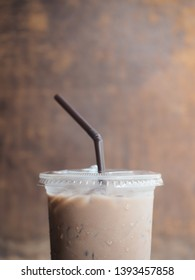 Chocolate drink in plastic glass with wooden background