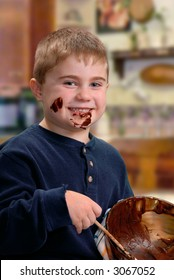 Chocolate drips from happy face of young boy as he scrapes the last of the cake batter from a bowl.