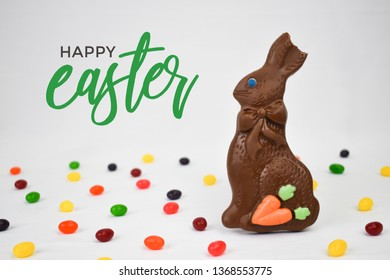 Chocolate Easter Bunny, Jelly Beans Candy and Happy Easter Calligraphy Text on White Background, Copy Space, Horizontal