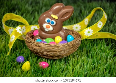 Chocolate Easter bunny in nest with colorful eggs on green grass and yellow ribbon