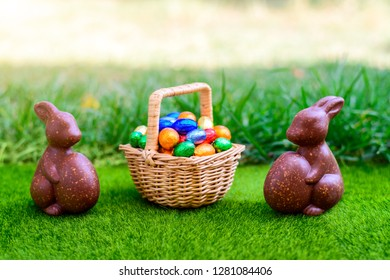 Chocolate Easter bunny with straw basket full of colourful eggs on green grass background