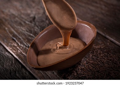 Chocolate Easter egg stuffed with chocolate sauce. - Shutterstock ID 1923237047