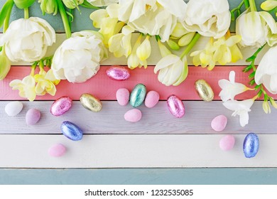 Chocolate Easter eggs, beautiful white tulips and yellow freesias on striped wooden background. Copy space.