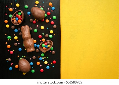 Chocolate easter eggs, easter bunny, colorful candy drops, on a black wooden background. The concept of a holiday and a happy Easter. Top view of a yellow substance with space for text