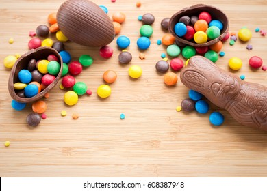 Chocolate Easter eggs, Easter bunny, multi-colored sweets candy on a textured wooden background. The concept of a holiday and a happy Easter. With space for text