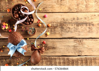 Chocolate Easter eggs with color ribbon bows on wooden background