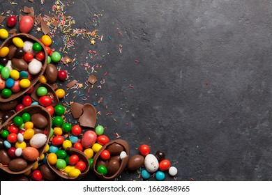 Chocolate easter eggs and colorful sweets on stone background greeting card. Top view. Flat lay with space for your greetings