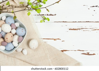 Chocolate Easter Eggs. Natural Linen Textile. Green Spring Leaves. White Wooden Scratched Background