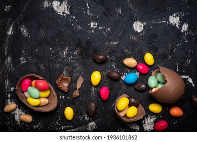 Chocolate Easter eggs on a dark wooden table with egg candies on a wooden table flat lay top view with copy space