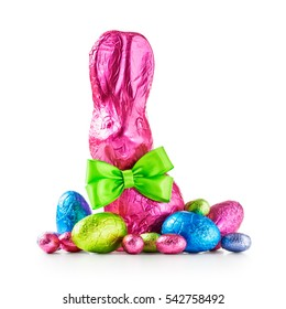 Chocolate easter eggs, rabbit with bow wrapped in pink foil and colorful candies isolated on white background clipping path included