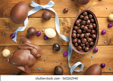 Chocolate Easter eggs, rabbit and sweets on wooden background