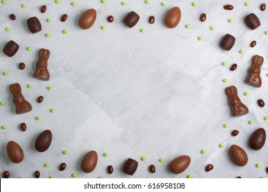 Chocolate easter eggs, rabbits, casks, green sweet candies on concrete background. Horizontal orientation, place for copyspace, flatlay, top view.