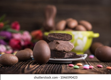 A chocolate Easter eggs with raw chocolate on a wooden backdrop
