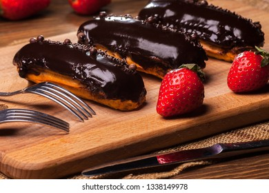 chocolate eclair with strawberry on wood table