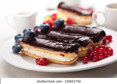 Chocolate eclairs with berries on white plate