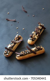 Chocolate eclairs with calamelized nuts, on dark background.
