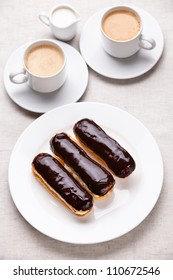 Chocolate eclairs with coffee on white textured background