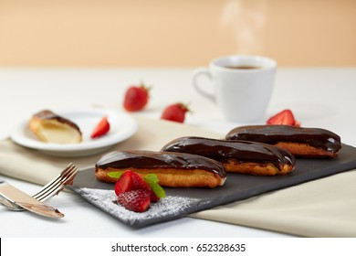 Chocolate eclairs with fresh strawberries on black Shale. Eclairs dessert with Berries and coffee on white background.