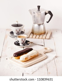 Chocolate eclairs on board on white textured background