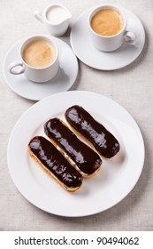 Chocolate eclairs on plate on white textured background