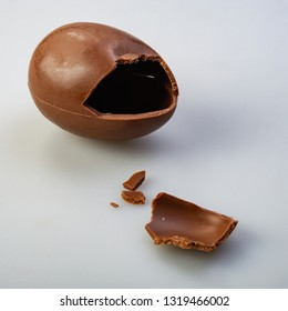 Chocolate egg candy broken on gray background. Web banner.