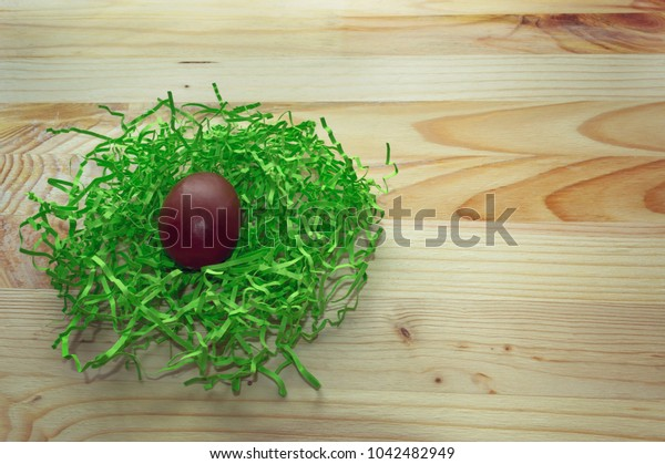 chocolate egg in green nest on wooden background