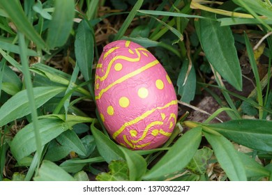 Chocolate egg wrapped in colored paper hidden in grass for Easter