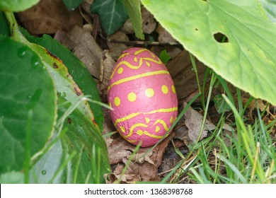 Chocolate egg wrapped in pink paper hidden in grass for Easter