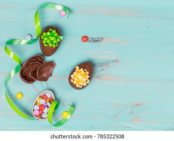 Chocolate eggs on color wooden background
