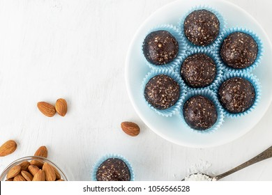 Chocolate energy bites with nuts, cocoa powder, dates and coconut flakes. Top view with copy space.