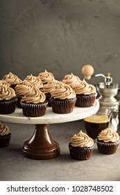 Chocolate espresso cupcakes on a cake stand with coffee beans