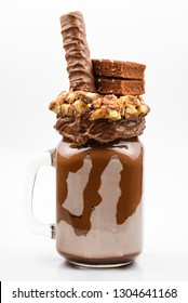 Chocolate extreme milkshake with brownie cake, chocolate paste and sweets. Crazy freakshake food trend. Copy space