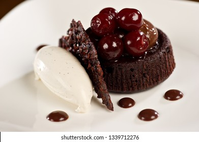 Chocolate Flourless Torte with chocolate sauce, cherries and gelato served on a white plate