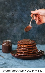 Chocolate fluffy pancakes with chocolate sauce. Blue background.
