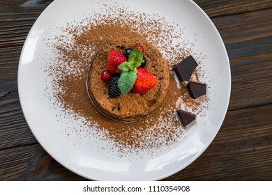 Chocolate fondant (lava cake) decorated with strawberries and cocoa powder on a wooden background
