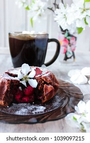 Chocolate fondant muffin with raspberry filling on wooden light background surrounded by spring blossom tree sakura and petals and cup of hot chocolate with marshmallows
