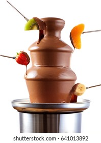 Chocolate fondue fountain with fresh tropical fruit on forks being dipped in the rich creamy sauce in a side view isolated over white