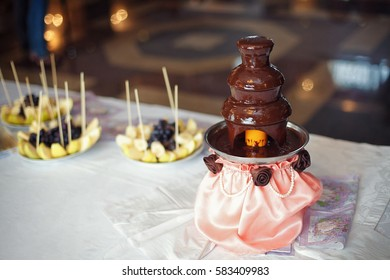 Chocolate fondue fountain with prepared fruits on table.