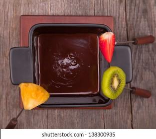 Chocolate fondue with fresh fruits on wood
