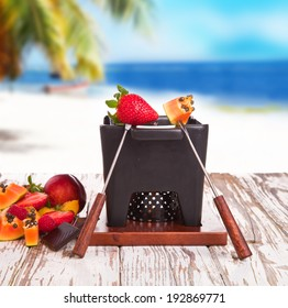 Chocolate fondue and fresh fruits on wooden table with tropical beach.