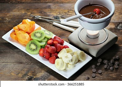 chocolate fondue with fruits assortment on wooden background