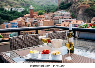 Chocolate fondue with fruits served in a terrace of restaurant. Tbilisi old city on background