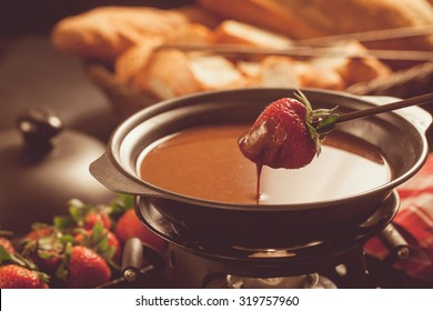 Chocolate fondue with oven on wooden table