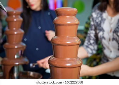 Chocolate fountain with fruits. Children birthday party . Homemade chocolate fountain fondue with marshmallow on a skewer dripping in chocolate sauce on blurred background and copy space .