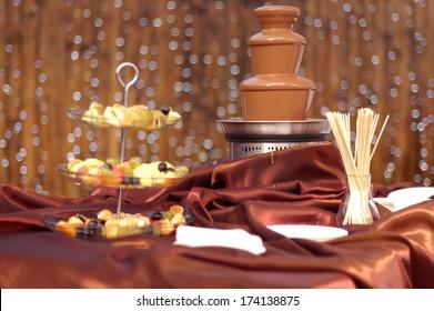 Chocolate fountain on the silk tablecloth the restaurant