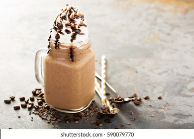 Chocolate frappe coffee with whipped cream and syrup on light background with copy space