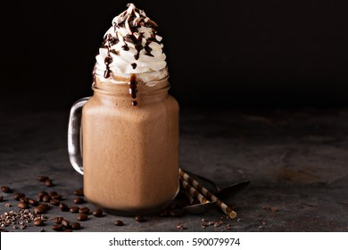 Chocolate frappe coffee with whipped cream and syrup on dark background