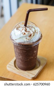 Chocolate frappe with whipped cream on wooden background