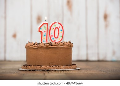 Chocolate frosted cake with wood background and table with ten candle for a 10th birthday