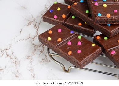 chocolate fudge brownies with candy pieces on cooling rack